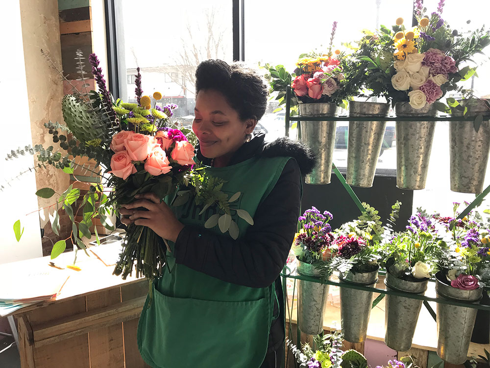 A woman creating a floral arrangement