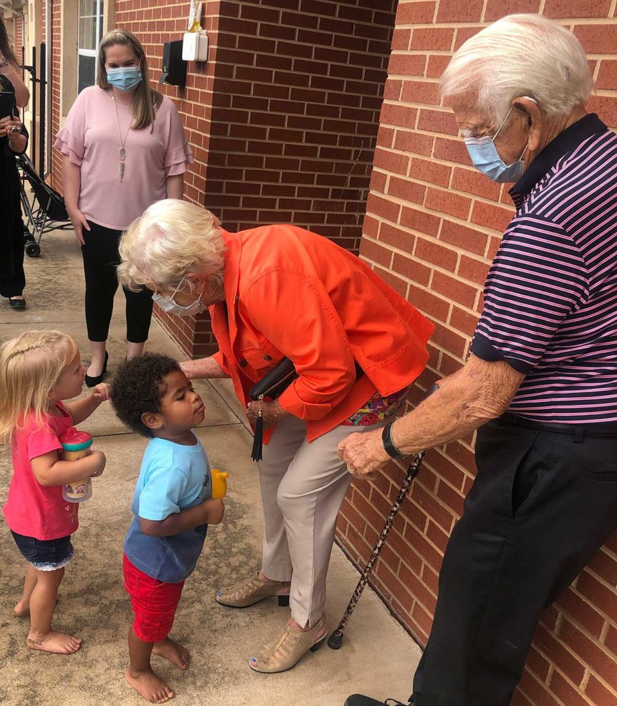 An older woman and man interacting with children