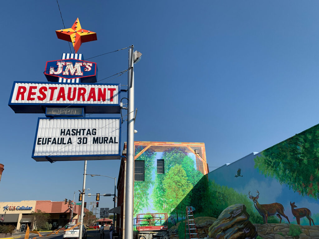 JM's restaurant which features a mural of wildlife in a forest setting